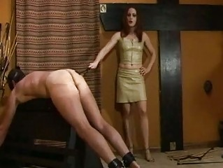 Sexy redhead mistress spanks slaves ass with different things